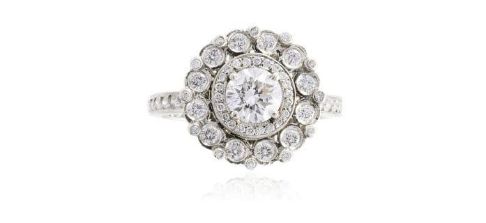 Erica Courtney  ring of prong set halo of melee diamonds surrounded by a cluster of bezel set diamonds.